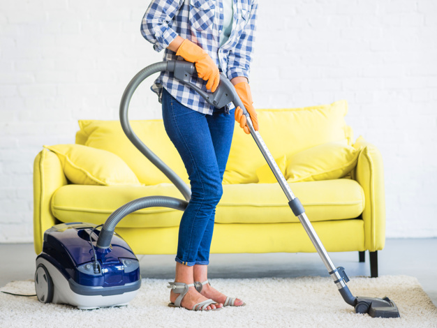 woman cleaning carpet with vacuum
